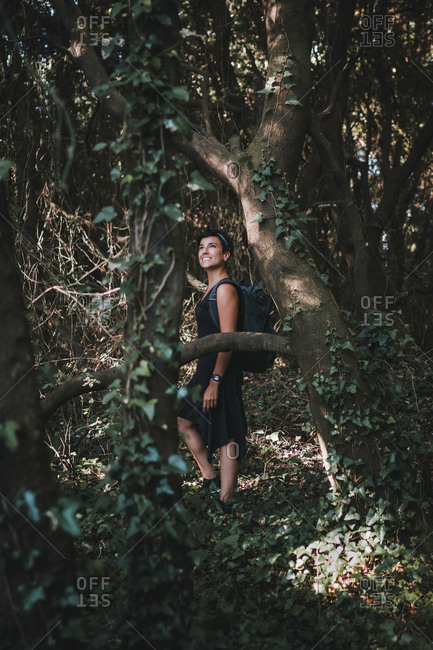 Full body portrait of a beautiful woman smiling and admiring nature while hiking in the forest wearing a backpack and a dress in the woods surrounded by trees
