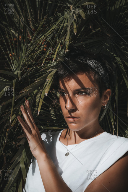 Portrait of a beautiful serious woman with short hair peeking through the leaves of a plant looking away with green leaves in the background and sunlight on her face