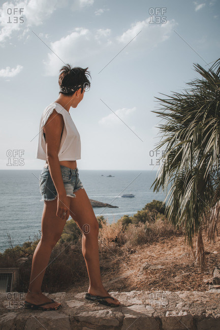 Attractive woman with short hair looking at the sea while walking on top of a cliff in Ibiza wearing denim shorts