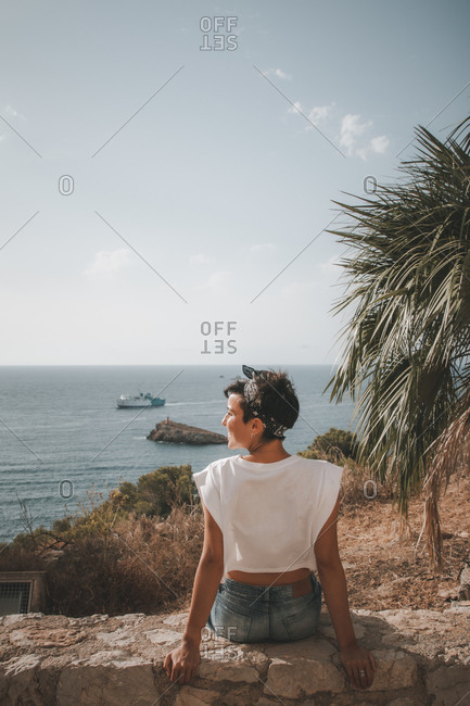 Beautiful woman with short hair looking at the sea smiling while sitting down over a cliff in Ibiza wearing denim shorts. Rear view