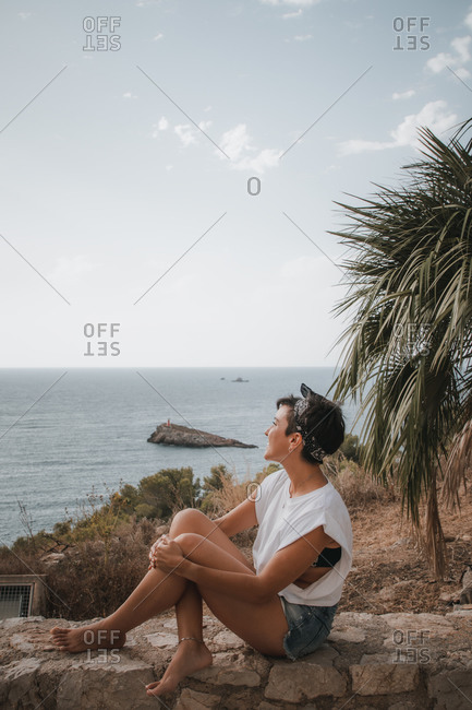 Beautiful woman with short hair looking at the sea smiling while sitting over a cliff in Ibiza wearing denim shorts