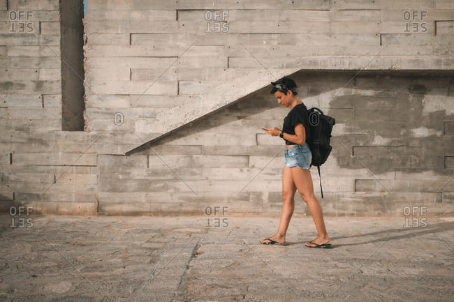 Attractive woman with short hair wearing summer clothes and a backpack walking while looking at her phone and texting
