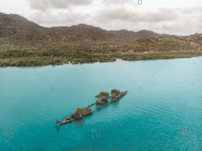 Aerial view of a shipwreck with trees growing on it, located off the coast on Magnetic Island,  Queensland, Australia