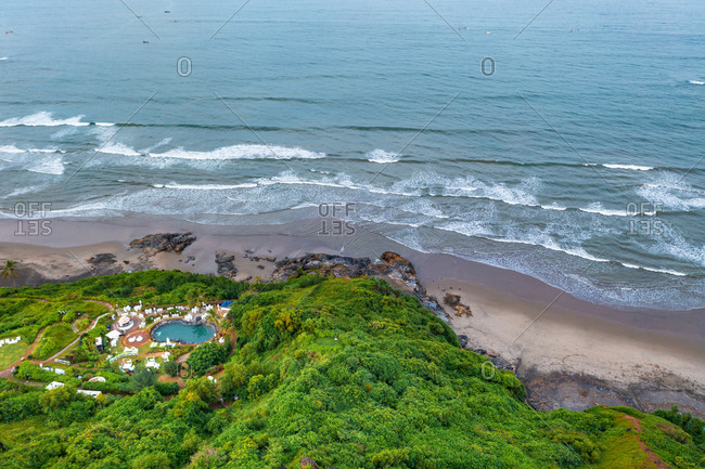 Aerial view of resort with pool on the coast of Goa, India.