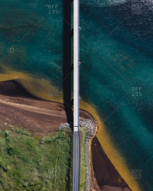 Aerial view of bridge on glacial river Olfusa coming down from the mountains to meet the ocean, Reykjanes Peninsula, Iceland.