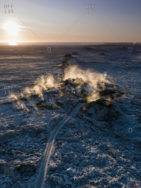Aerial view of a steaming row of volcanic craters during sunset, releasing geothermal heat centuries after eruption, Eldvorp, Reykjanes Peninsula, Iceland