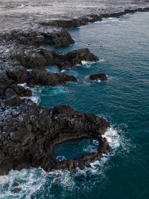 Aerial view of Brimketill geothermal lava rock pool, hanging off the edge of a black volcanic cliff in Southern Reykjanes Peninsula, Iceland.