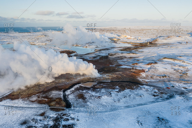 Aerial view of geothermal steam pot and geothermal power plant in the background, Gunnuhver, Reykjanes Peninsula, Iceland