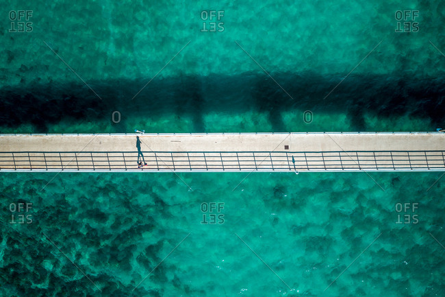 Aerial view of a person walking on a bridge surrounded by turquoise water in Vrsar, Croatia