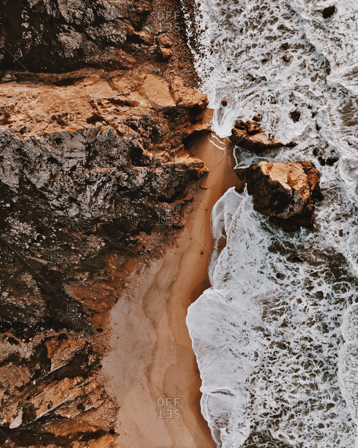Aerial view of waves breaking on a coast with unique rock formation, Praia da Ursa, Lisbon region, Portugal.