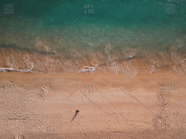 Aerial view of a girl in hat sitting on the beach, Comporta, Setubal district, Portugal.
