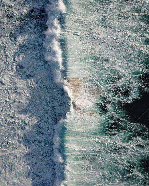 Breathtaking view of a stormy turquoise ocean, Praia da Crismina, Portugal