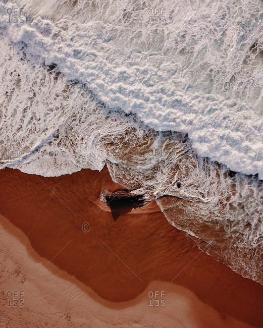 Aerial view of an empty beach, that called Praia da Crismina, Portugal. Amazing big waves with foam and golden sand.