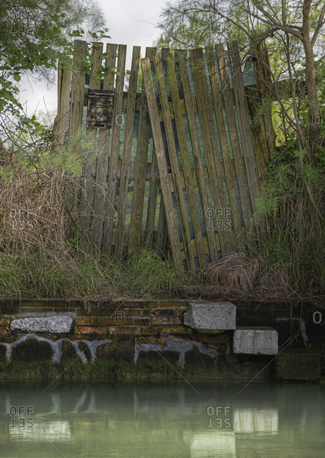 Dilapidated wooden fence on canal waterfront.