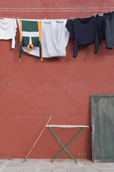 Clothes hanging on laundry line on wall.