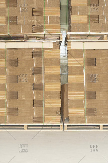 Pallets of flat folded cardboard boxes.