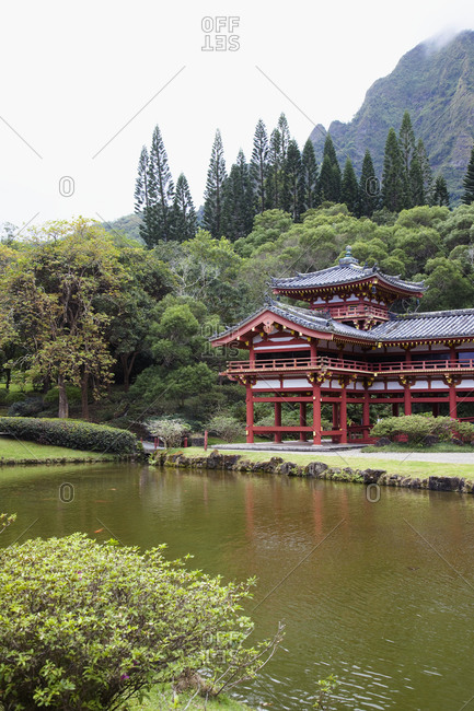 Pagoda on verge of pond with mountain behind.