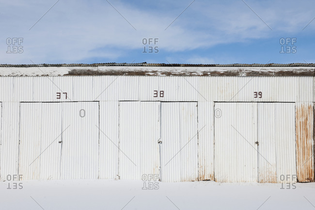 Numbered doors on corrugated metal storage building.