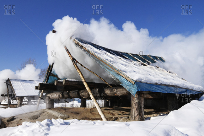 Wooden shack covered with clouds in snow.
