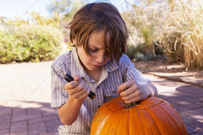 Young boy carving pumpkin on patio.
