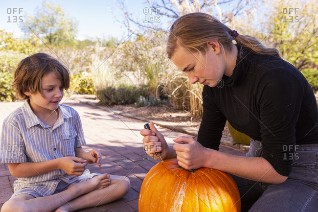 Teenage girl and her younger brother carving pumpkins on patio.