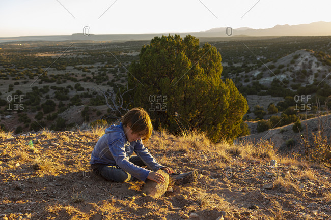 Young boy in Galisteo Basin at sunset with his English Cream Golden Retriever