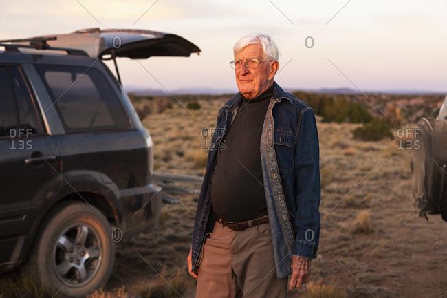 Senior man standing between SUV cars at sunset, Galisteo Basin