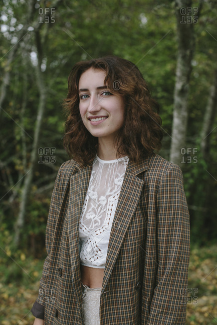 Portrait of happy seventeen year old girl standing in lush forest in Fall, Discovery Park, Seattle, Washington