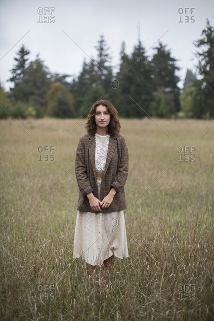 Portrait of seventeen year old girl wearing tweed  blazer, standing in field of tall grasses, Discovery Park, Seattle, Washington