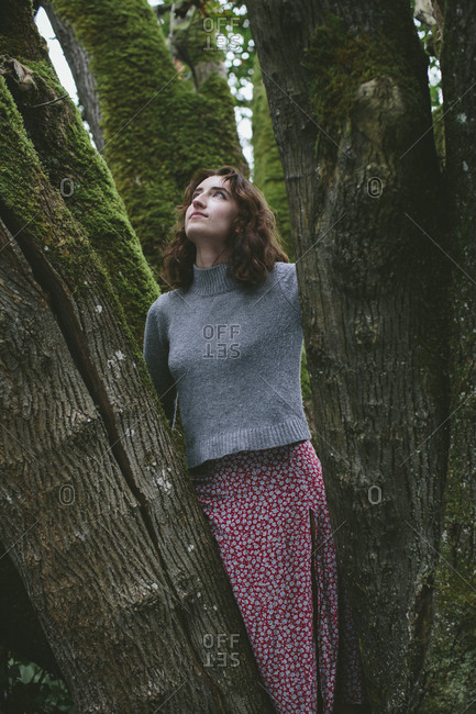Portrait of seventeen year old girl standing in front of mossy Bigleaf maple tree