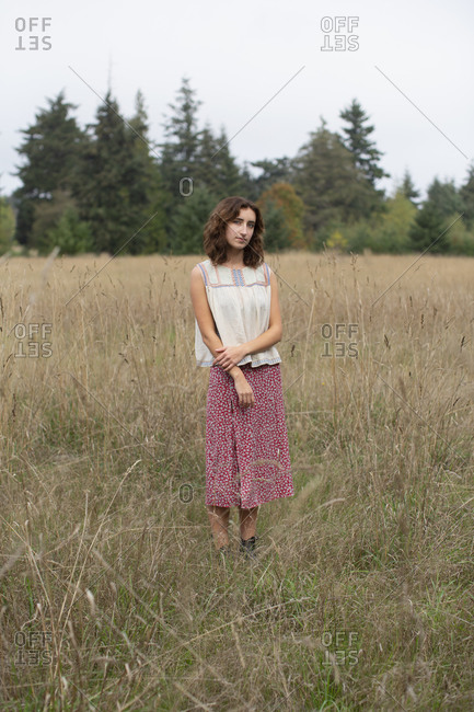 Portrait of seventeen year old girl standing in field of tall grasses, Discovery Park, Seattle, Washington