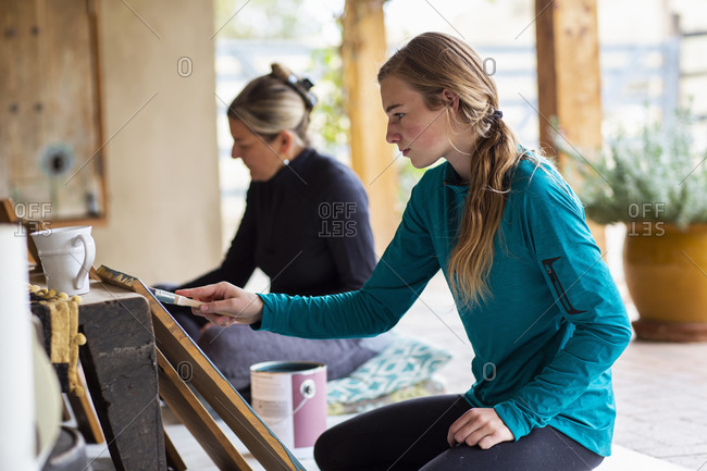 Teenage girl and her mother painting wooden shelves blue on a terrace