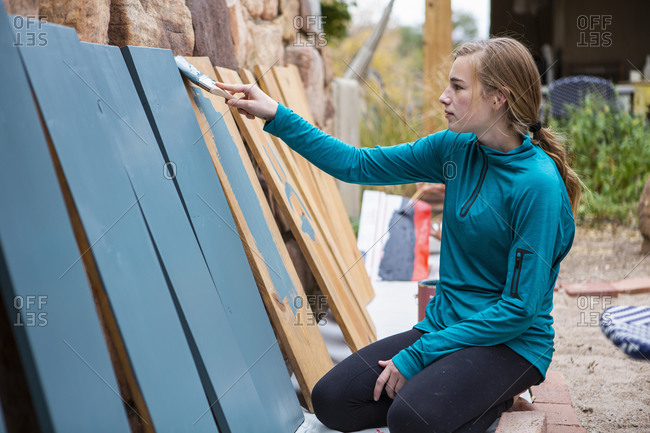 Teenage girl painting wooden shelves blue.