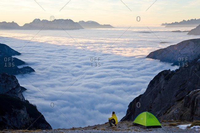 December 14, 2020: Man and tent above the clouds, Trentino-Alto Adige, South Tyrol in Bolzano district, Alta Pusteria, Hochpustertal, Sexten Dolomites, Italy