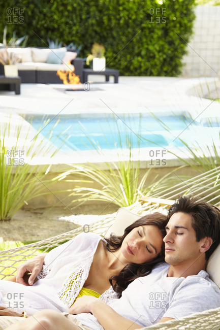 Happy young couple at home relaxing, sharing a hammock