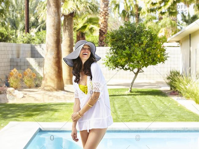 Young Hispanic woman in a white shirt over her bikini.