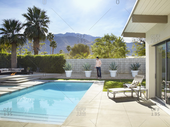 Man standing on a patio by a swimming pool
