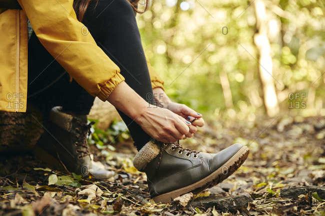 Close up of woman sitting on log tying shoe lace on woodland path