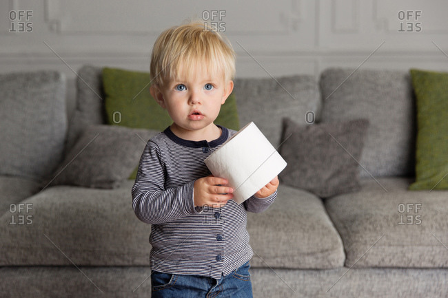 Cute toddler holding toilet paper roll at home