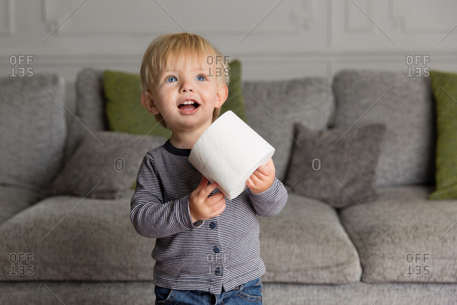 Happy toddler holding a roll of toilet paper at home