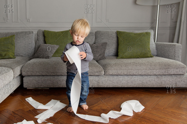 Cute young boy making mess with toilet paper in living room