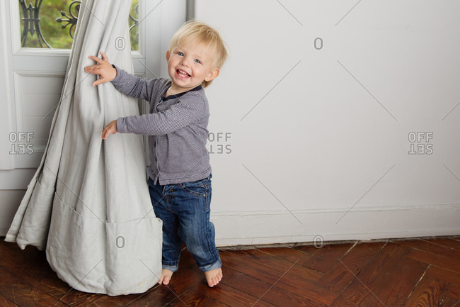 Happy toddler playing behind curtains at home