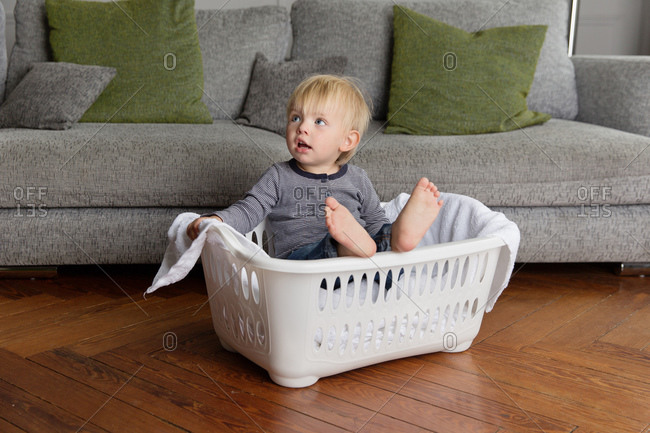 Cute toddler sitting in laundry basket in living room