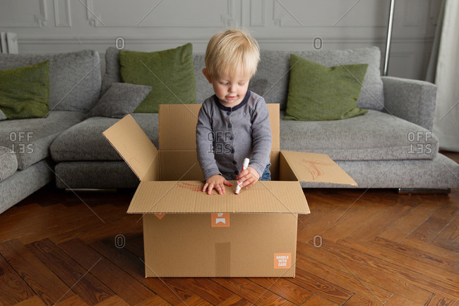 Cute toddler drawing on cardboard box
