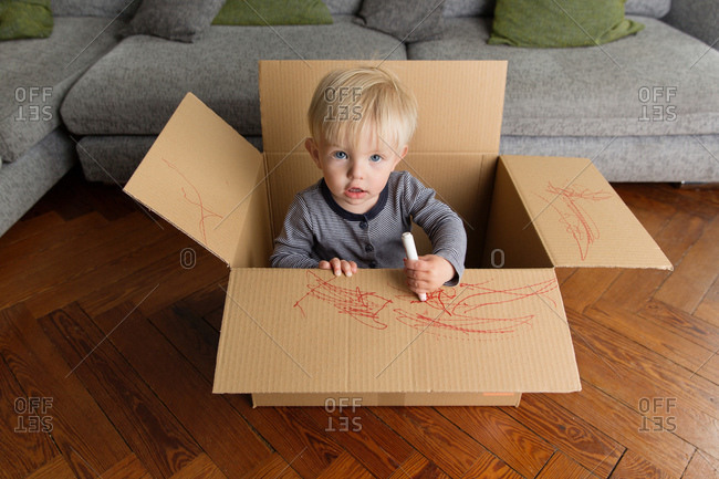 Cute baby boy drawing on cardboard box