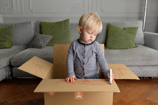 Toddler boy drawing on cardboard box
