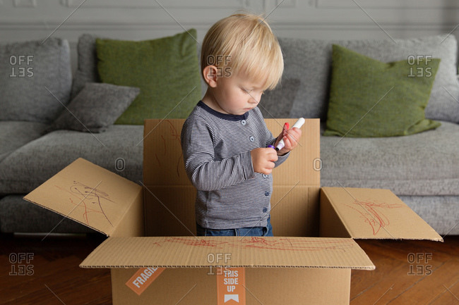 Toddler boy standing in cardboard box holding marker
