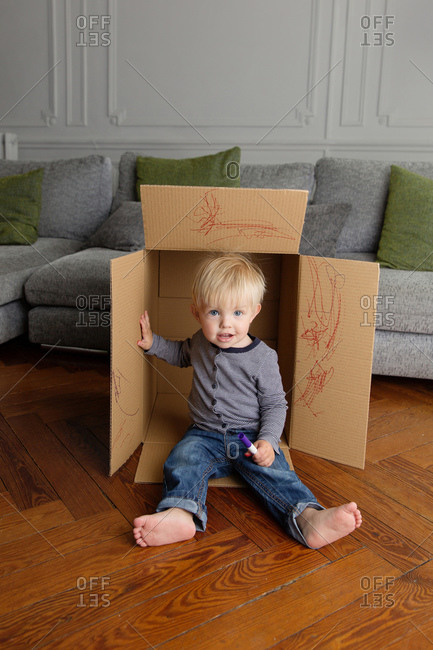 Toddler boy sitting in cardboard box holding marker