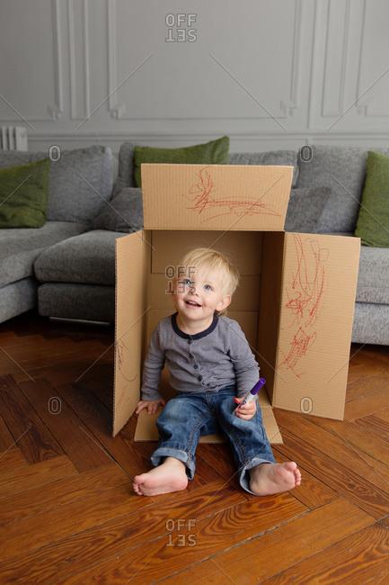 Smiling toddler sitting in cardboard box holding marker