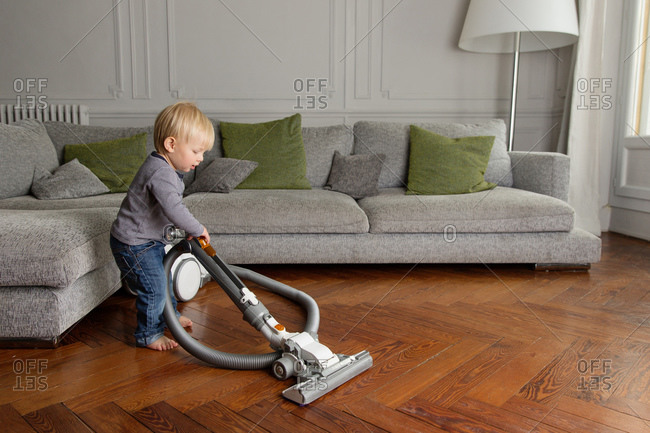 Cute toddler using vacuum on hardwood floor in living room